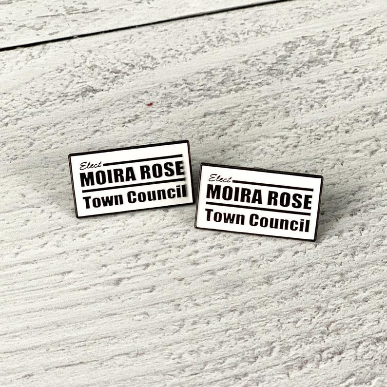 "The rectangular black and white pin that reads ""Elect Moira Rose Town Council"""