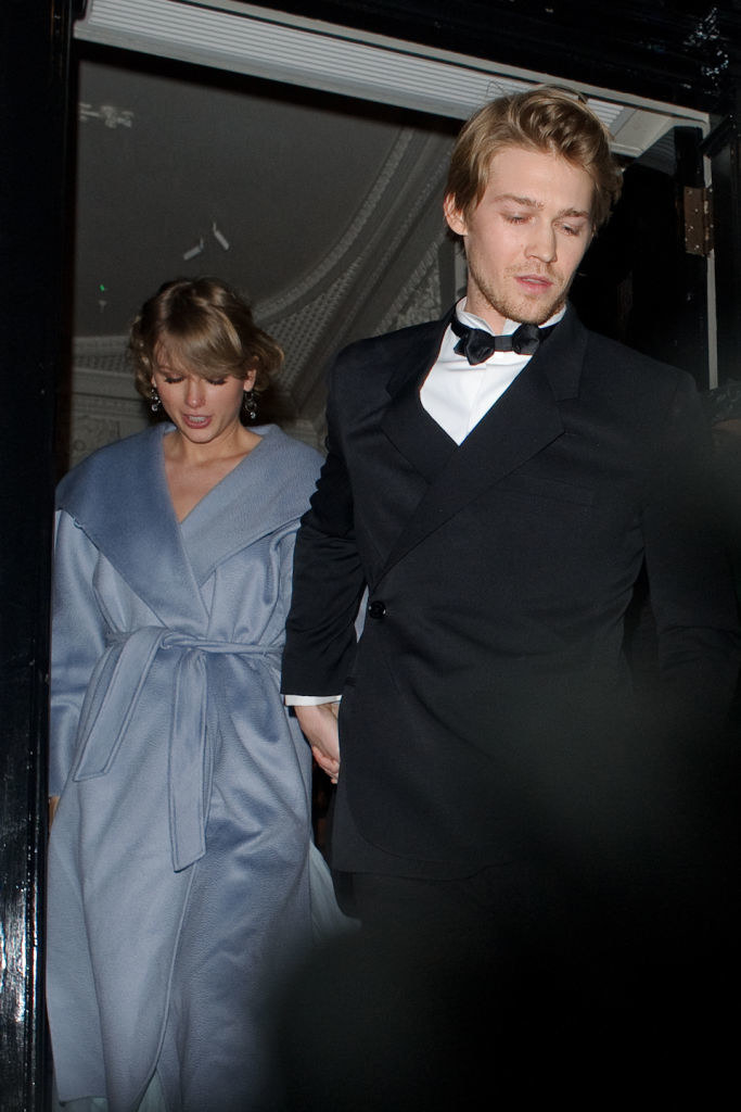 Joe Alwyn holding hands with Taylor Swift as the exit a building