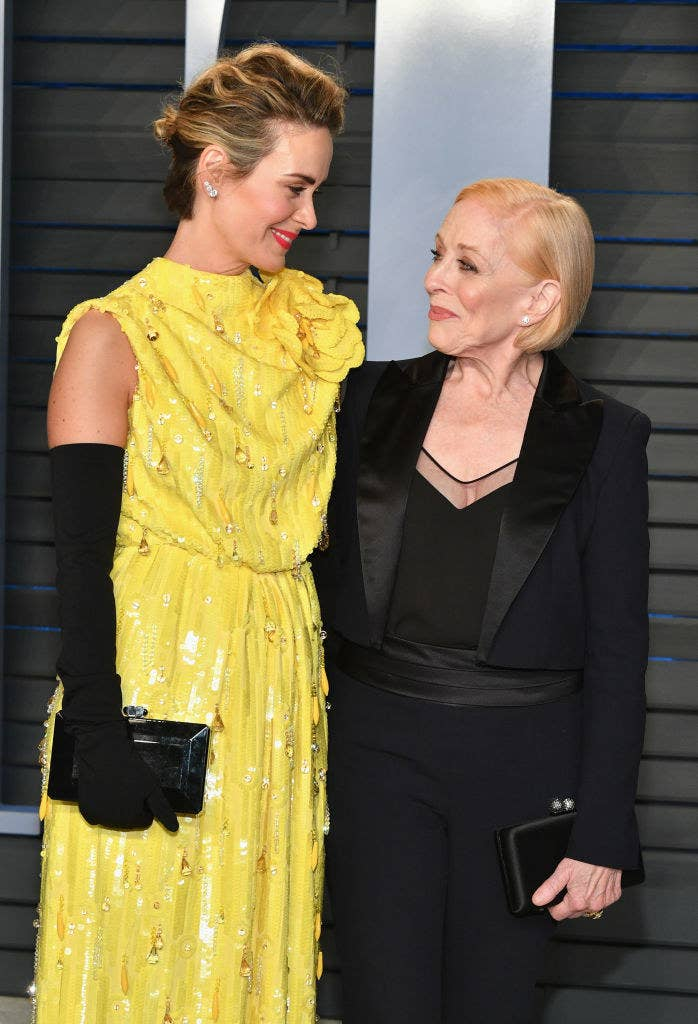 Sarah Paulson in a yellow dress  smiles at Holland Taylor in a black one