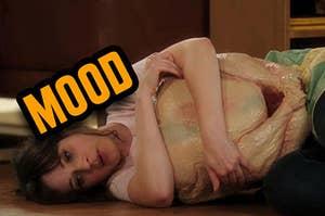 Jess on the floor hugging a frozen turkey