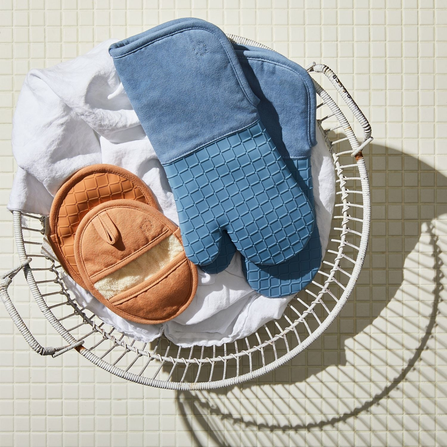 a set of silicone oven mitts and pot holders in a basket