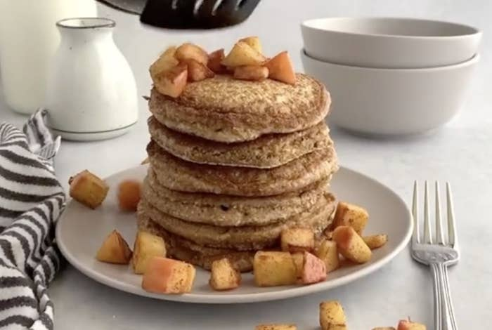A large stack of pancakes at a table setting