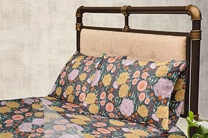 bed with floral print bed sheets on it