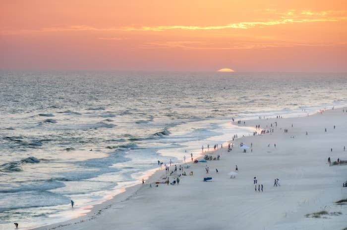 Orange beach's white sand and blue waters at sunset, dotted with people