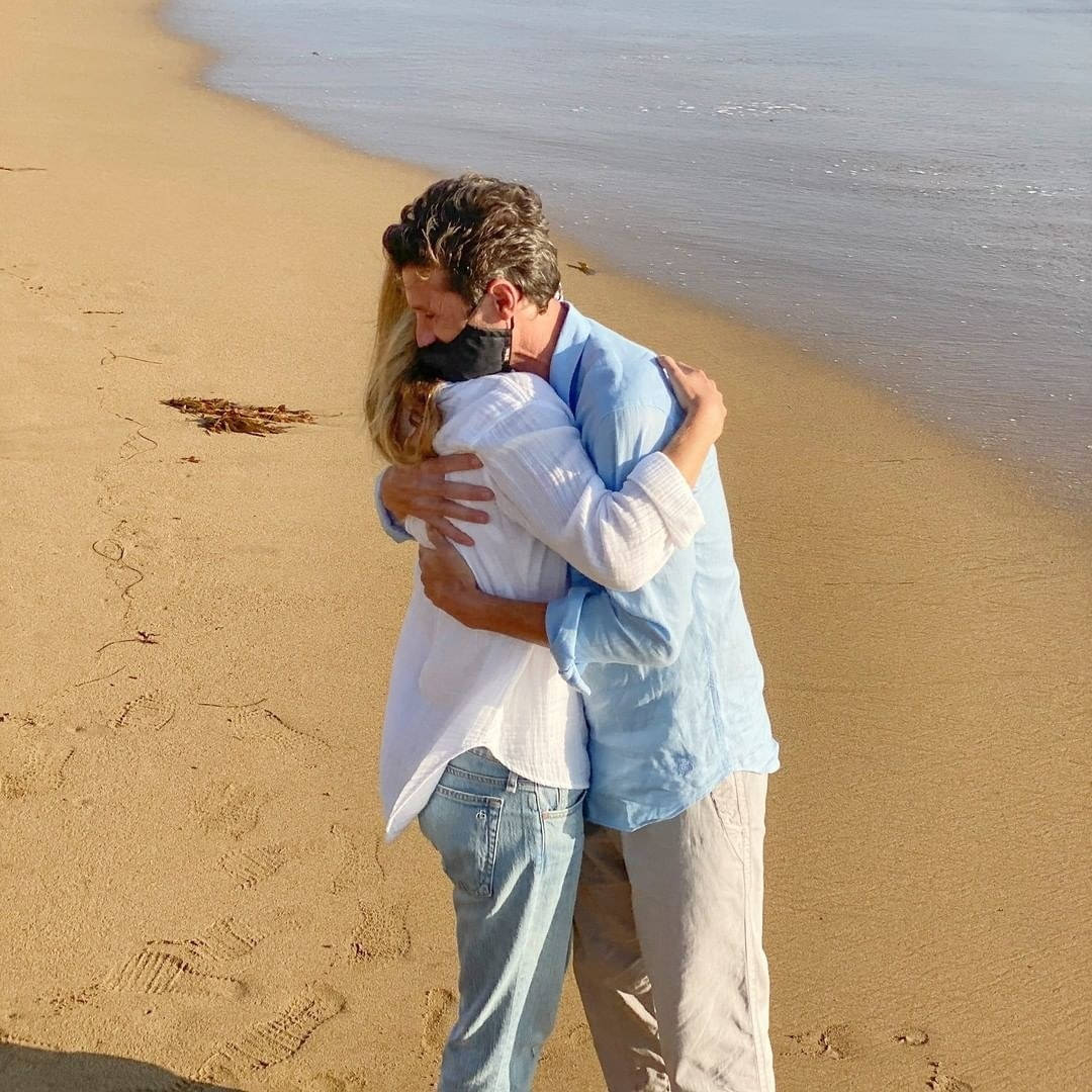 Ellen and Patrick hugging on a beach