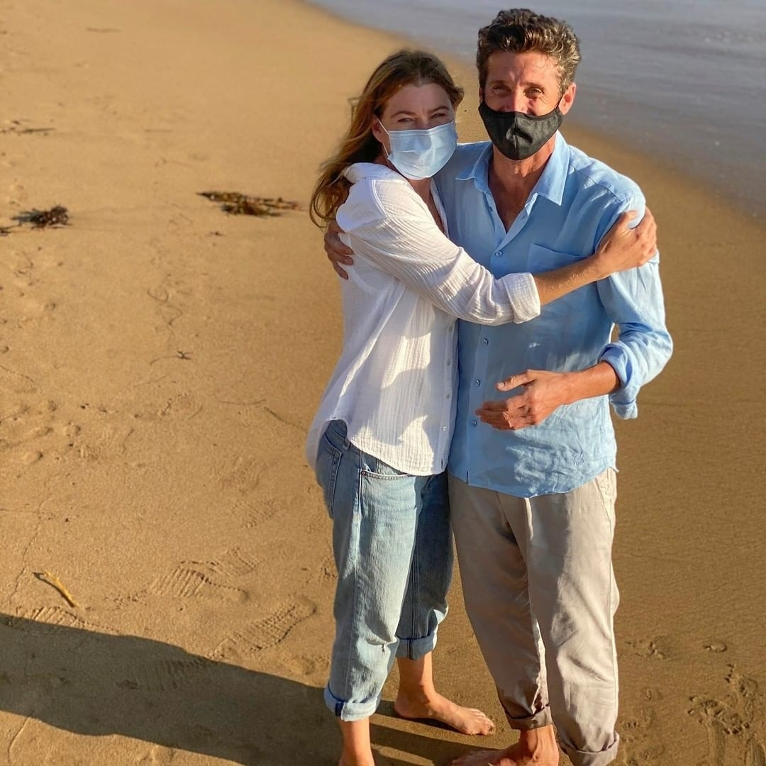 Ellen Pompeo and Patrick Dempsey hugging each other on a beach and wearing masks