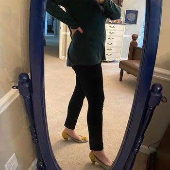 Reviewer wearing black jeans with heels and long top