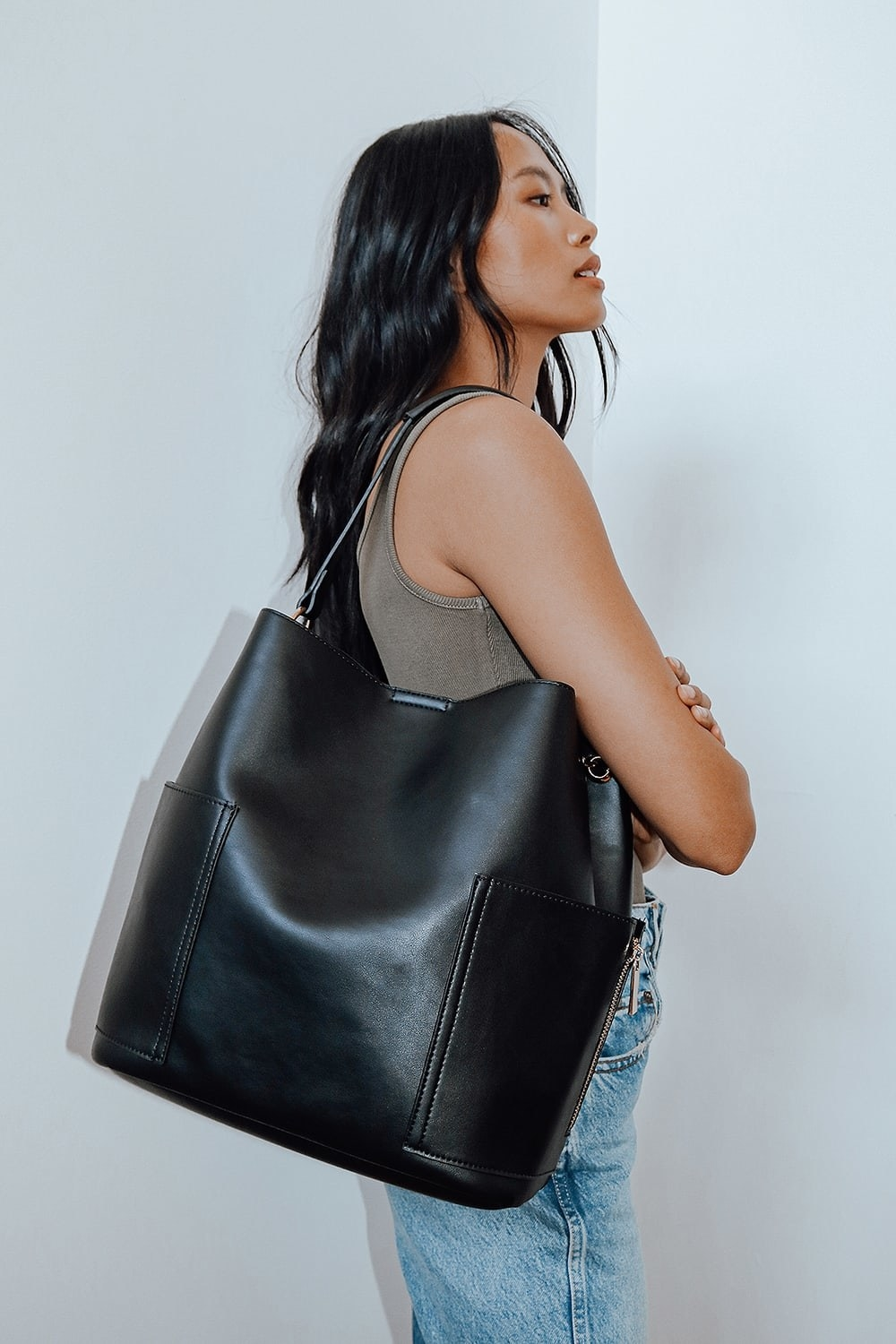 Model wearing black tote bag over shoulder
