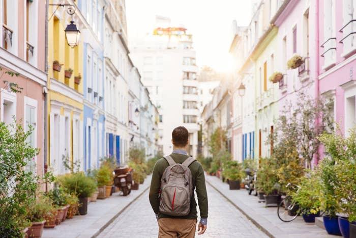 A man with a backpack walks down a pretty, foreign street