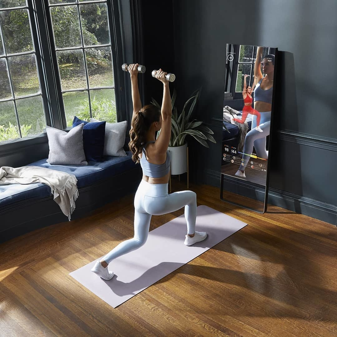 The rectangle-shaped mirror on a wall with a model on a yoga mat mirroring what the trainer is doing on the screen