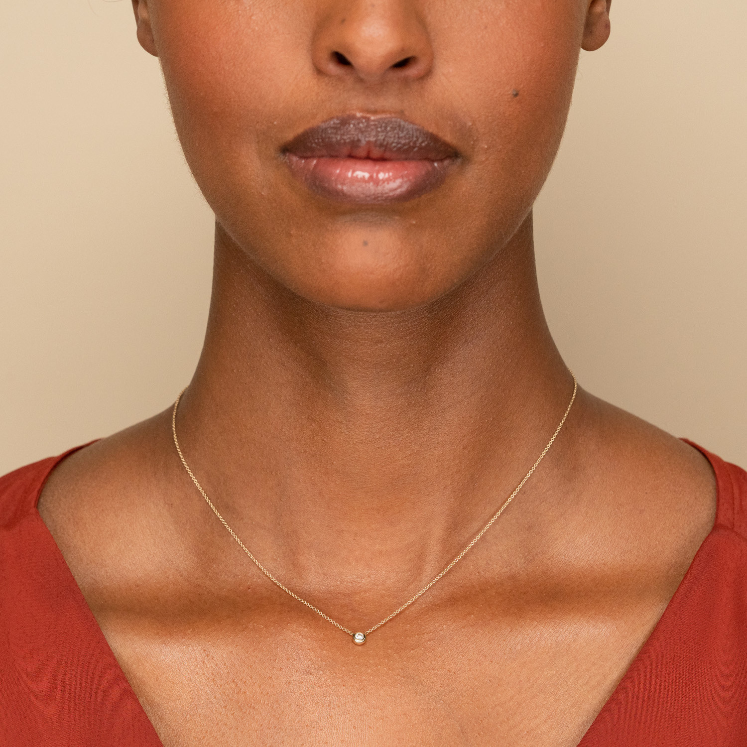 Small round diamond on a gold chain around a model's neck