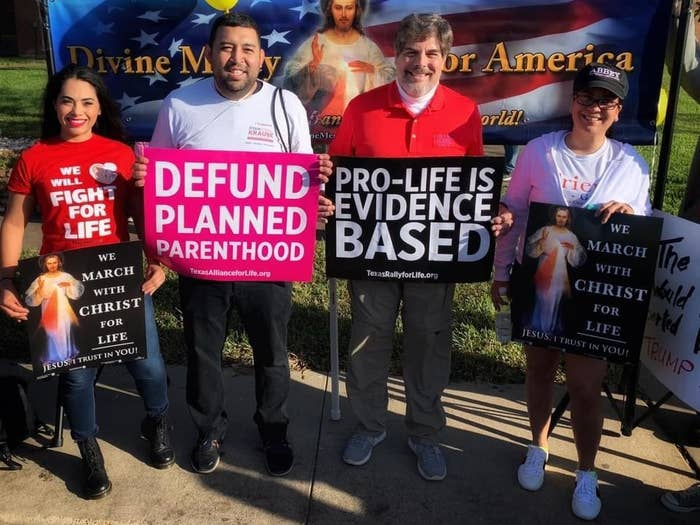 Protesters hold signs opposing abortion