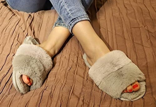 A pair of fluffy slippers with feet in them on a bed