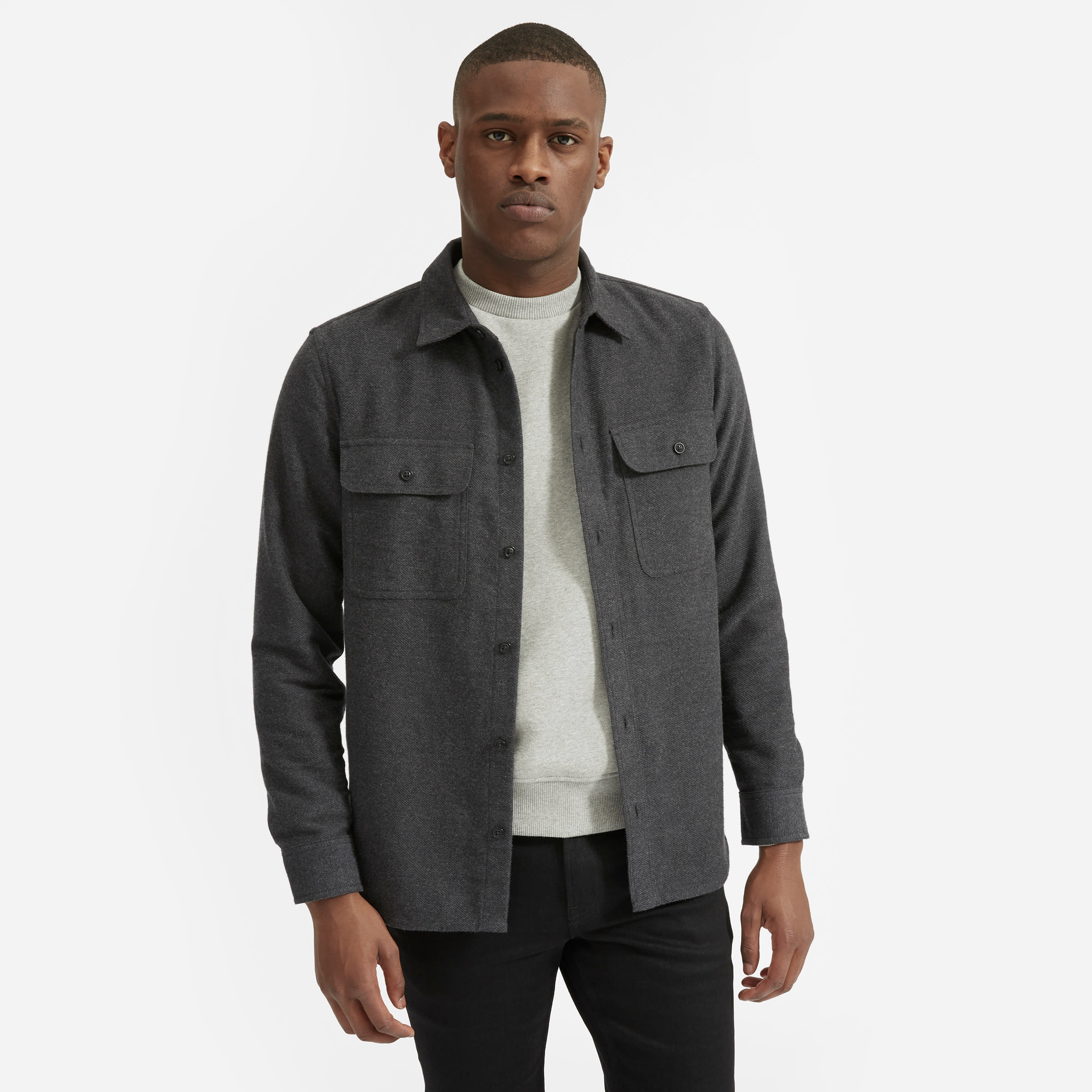 Model wearing the button-down shirt with buttoned pockets on each side in dark grey
