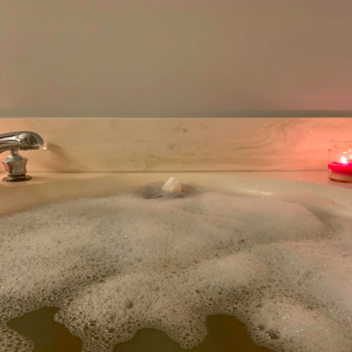 a reviewer's photo of their bubble bath with a candle next to it