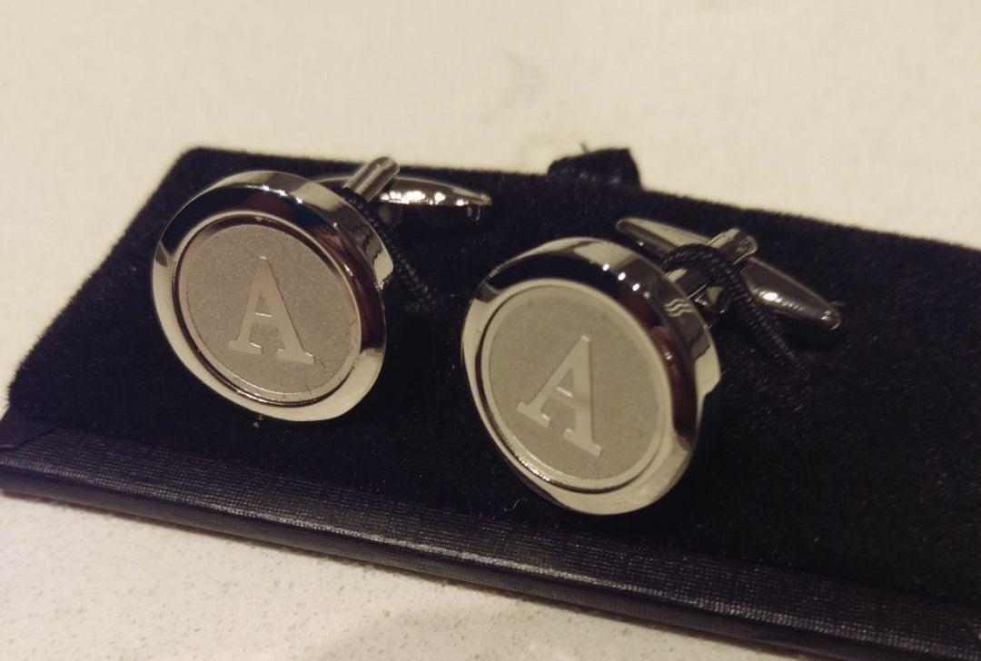 A reviewer's pair of the silver tone cufflinks in the letter A, with a rounded shape, outside lip around the engraving