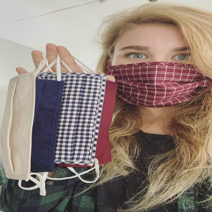 A reviewer wearing the plaid mask and holding up four other ones