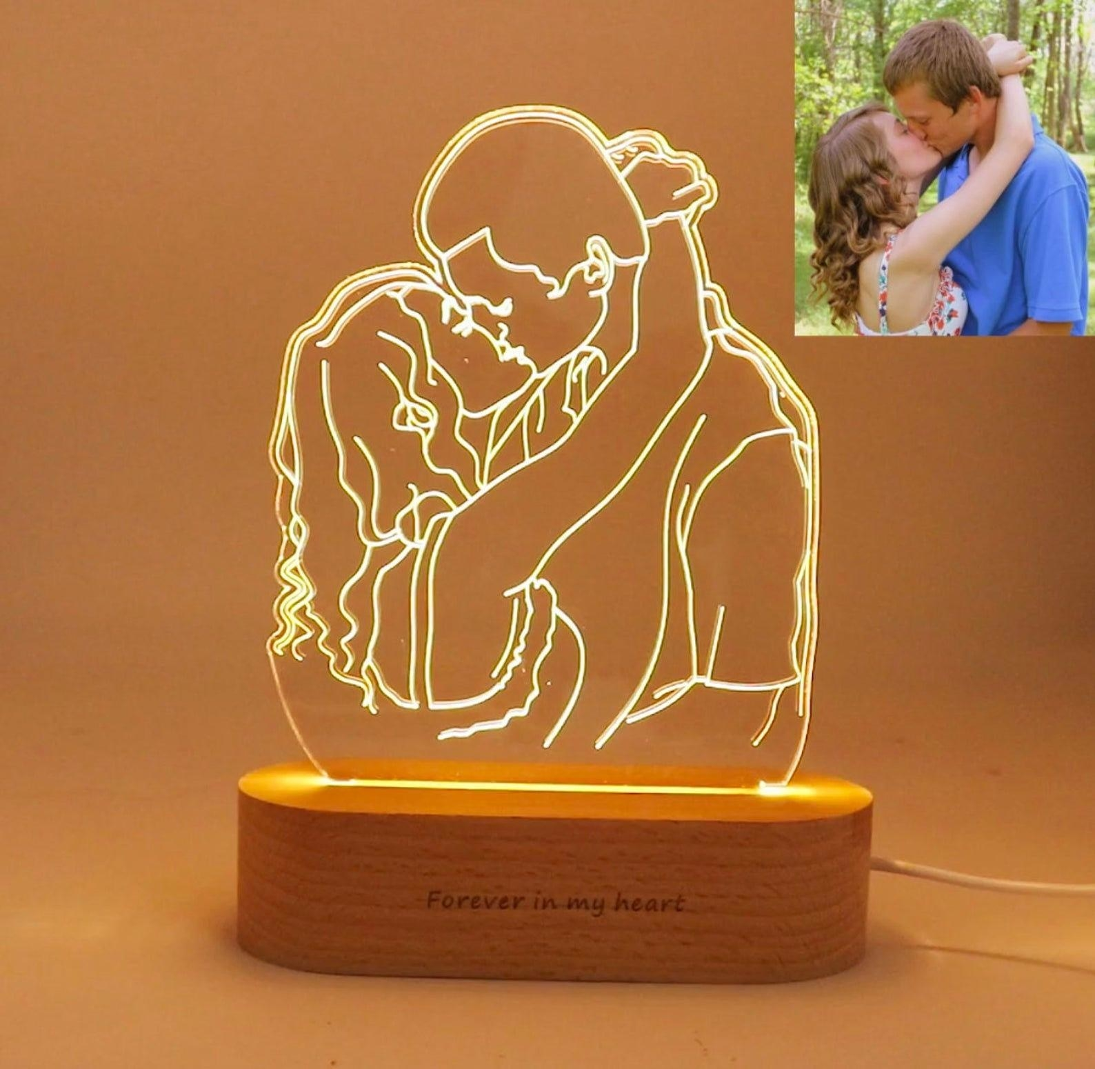 "The light with a personalized design of a couple kissing with the words ""Forever in my heart"" engraved on the wood base"