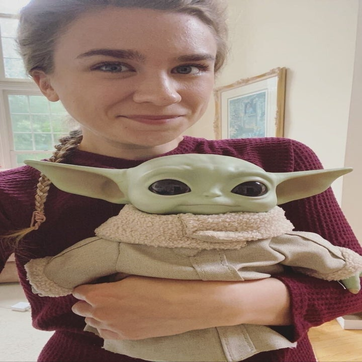 A reviewer holding the baby Yoda toy