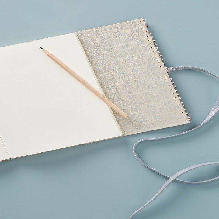 the journal comes with a pencil and closes with a strap