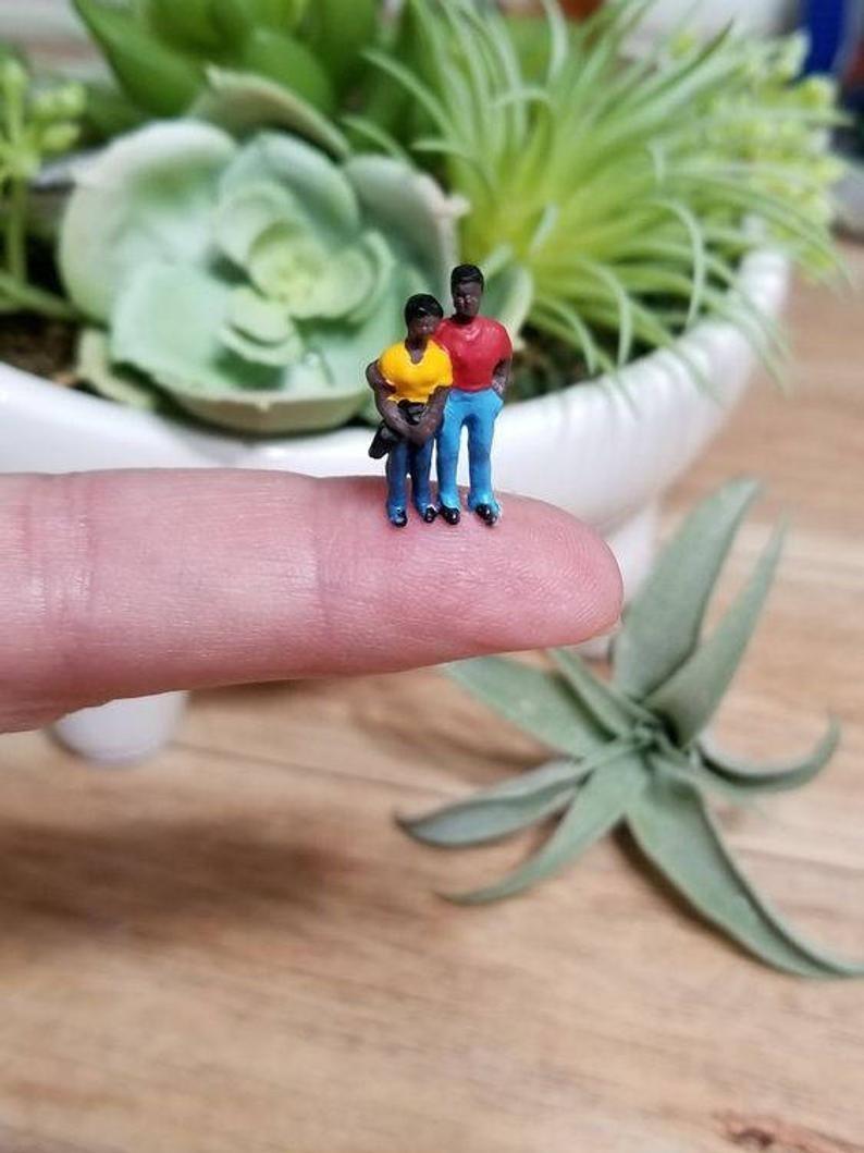 Finger holding a miniature black couple