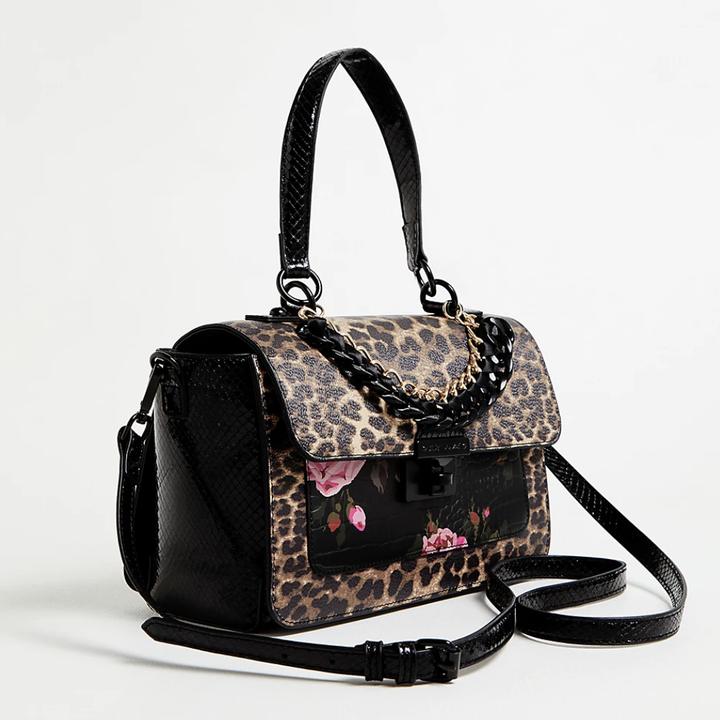 the satchel is leopard print and black with a hand strap and crossbody strap, and the front pocket has pink flowers on it