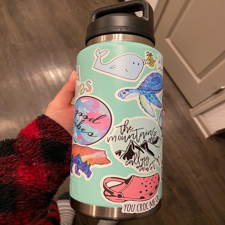 a reviewers water bottle covered in different stickers