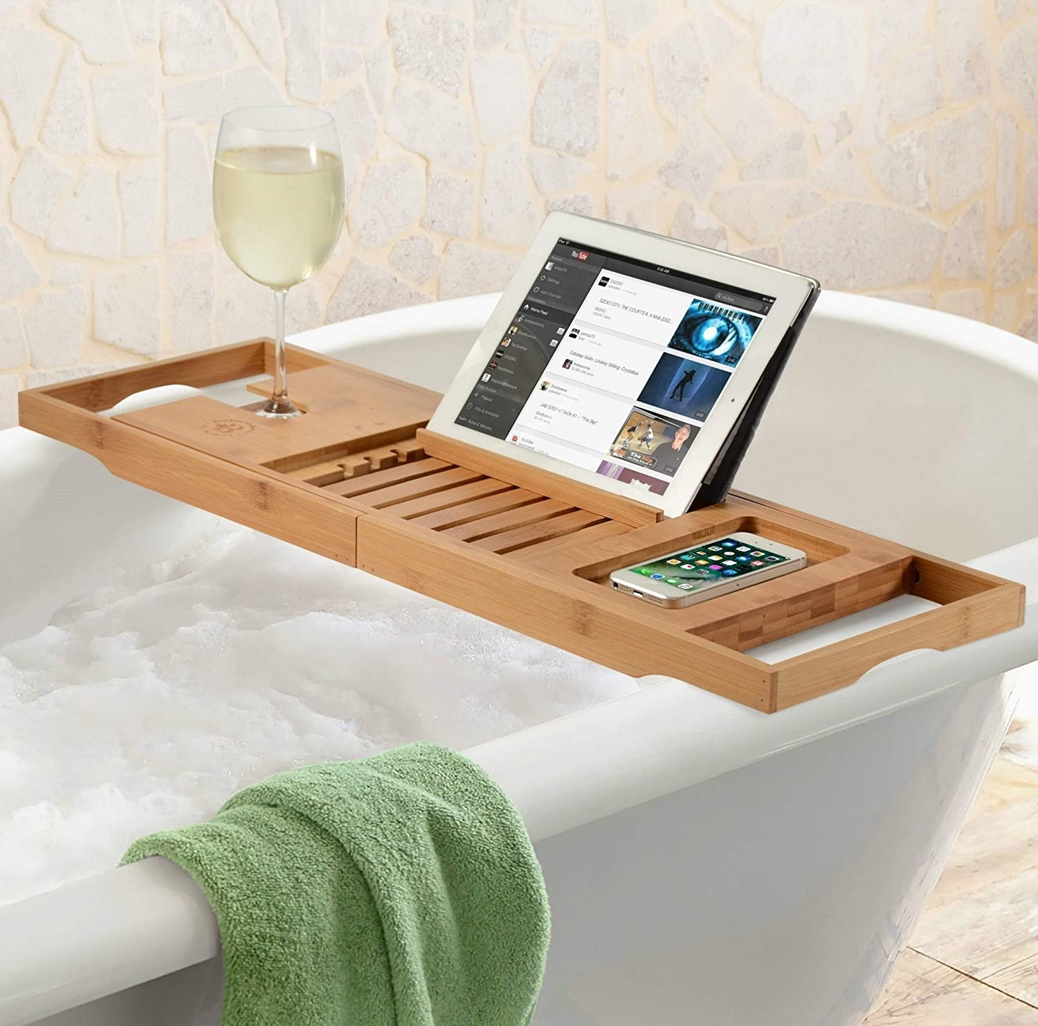 The bath caddy with a book, wine glass, and tablet on it