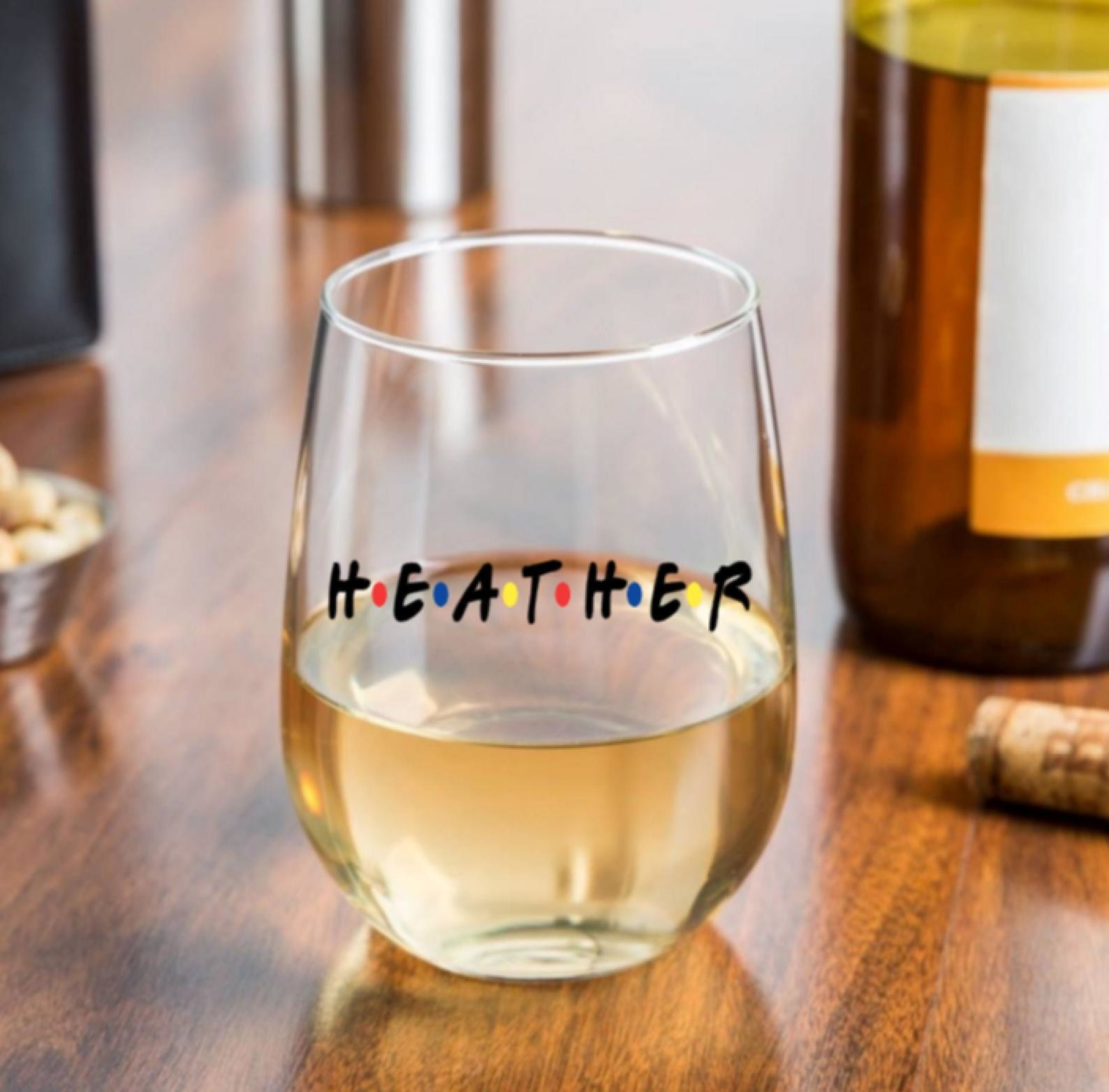"a stemless wine glass with the name ""heather"" written on it like the friends logo"