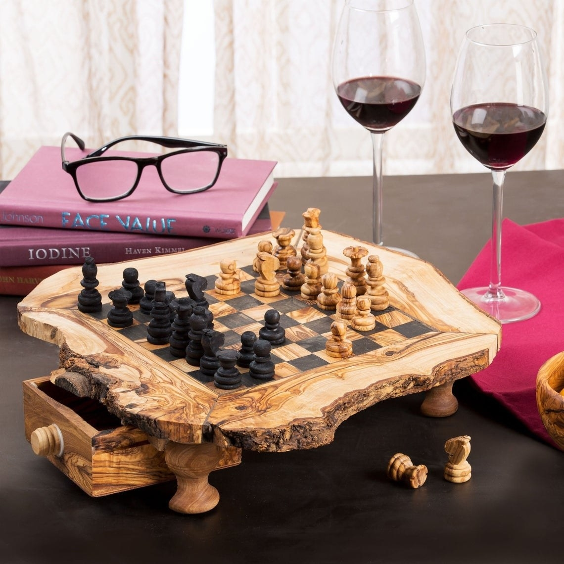 The chess board with pieces on top of it, there are wine glasses and books surrounding it