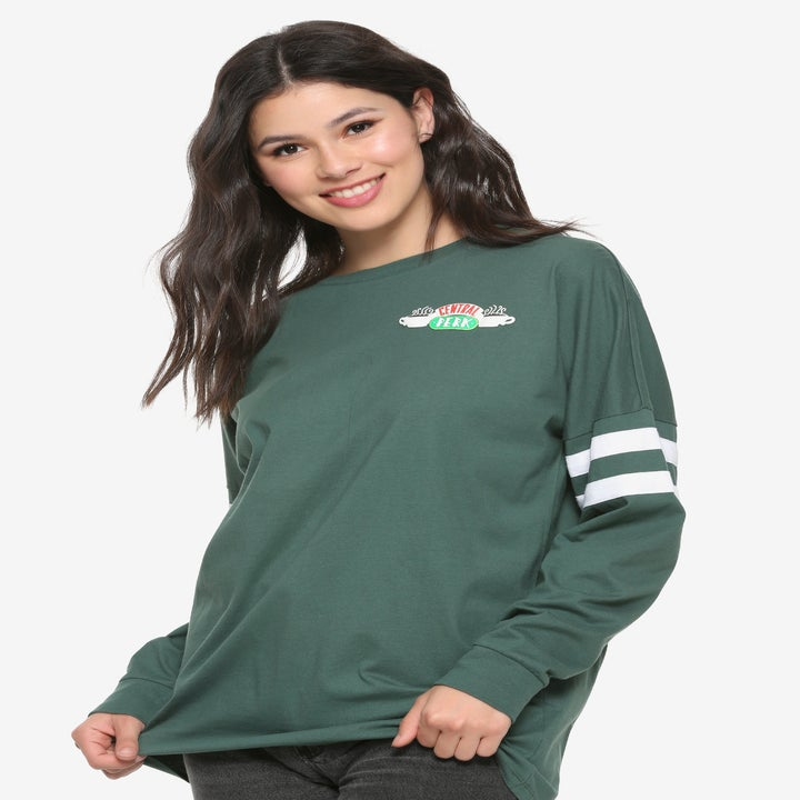 a model wearing a forest green long sleeve with two white stripes on each arm and the central perk logo in the top right corner