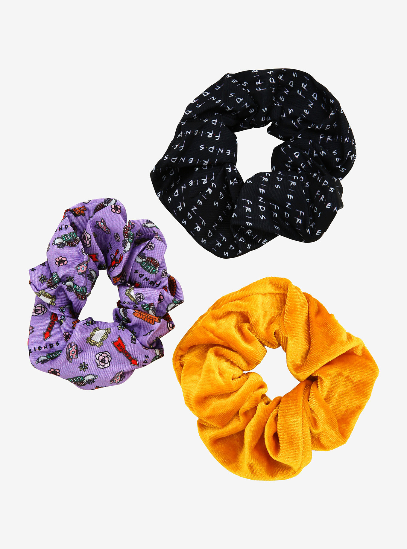 a black scrunchie with the friends logo all over it, a purple one with different icons from the show, and a yellow velvet scrunchie