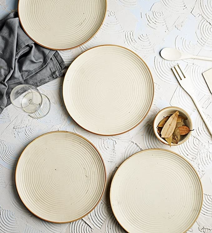 Beige ceramic dinner plates with a gold rim.