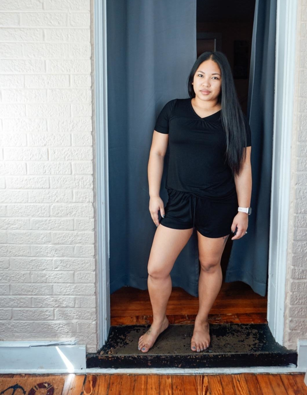 a reviewer wearing the t-shirt and shorts set in black