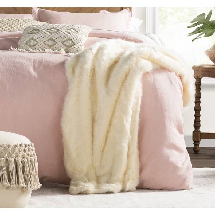 white faux fur blanket draped on a bed