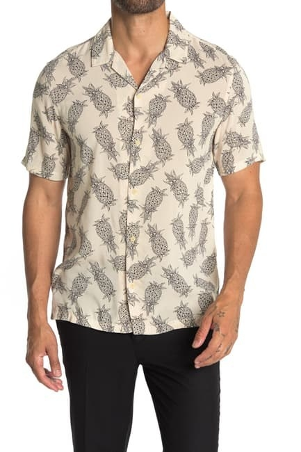 model wearing a button down off white shirt with a black pineapple print on it