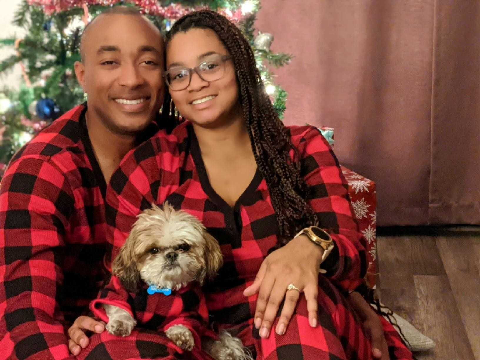 a couple and their dog wearing the red and black pajamas