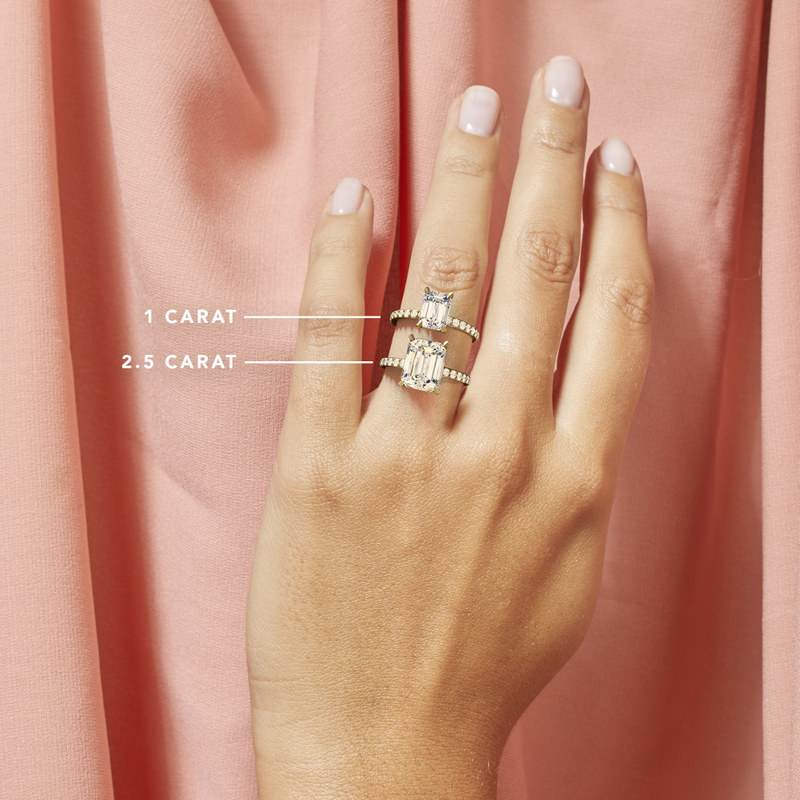 Model wearing a one carat and a two-and-a-half carat emerald engagement ring