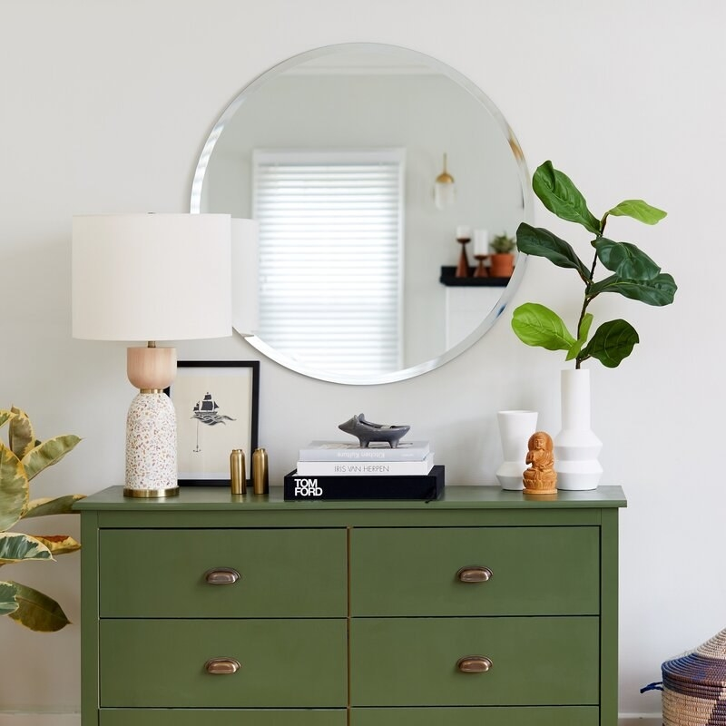 Round frameless mirror mounted on wall above dresser