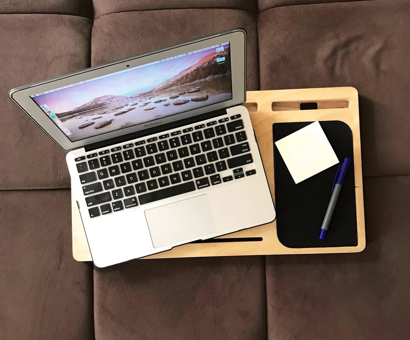 a laptop and notepad with pen on wooden tray
