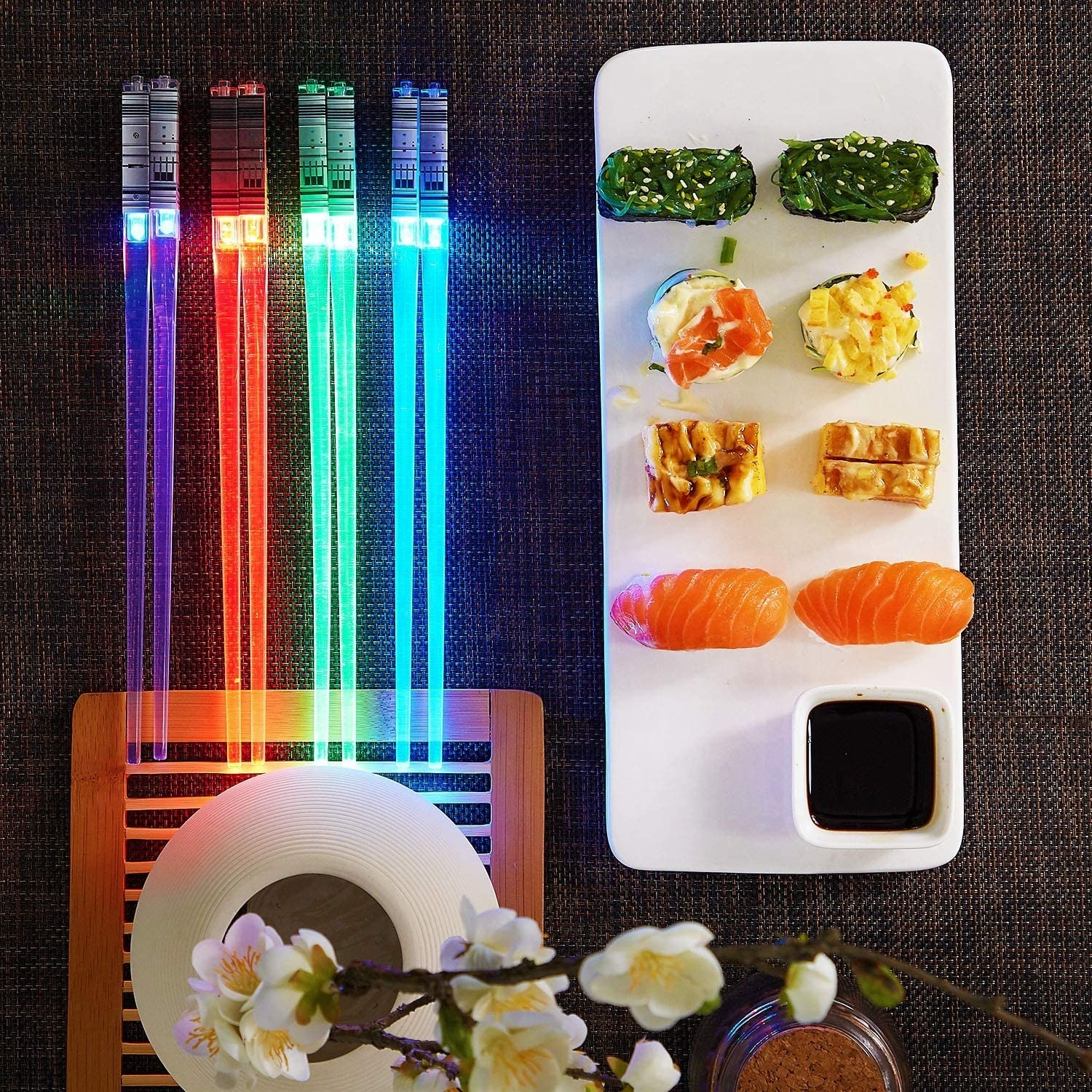 "four chopsticks on a table that light up and look like Light Sabers from ""Star Wars"""