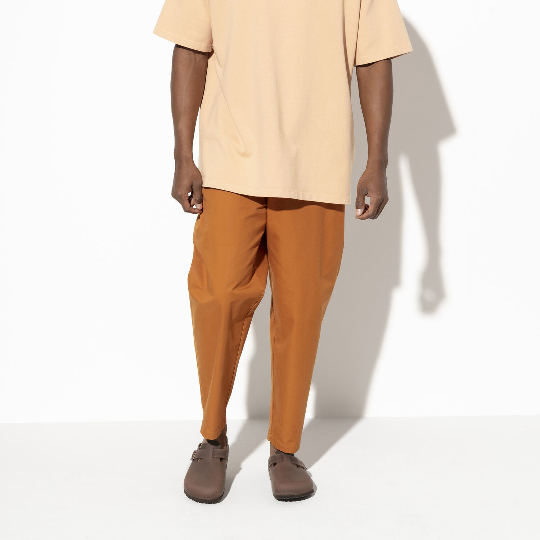 Model wearing Birkenstocks with orange pants