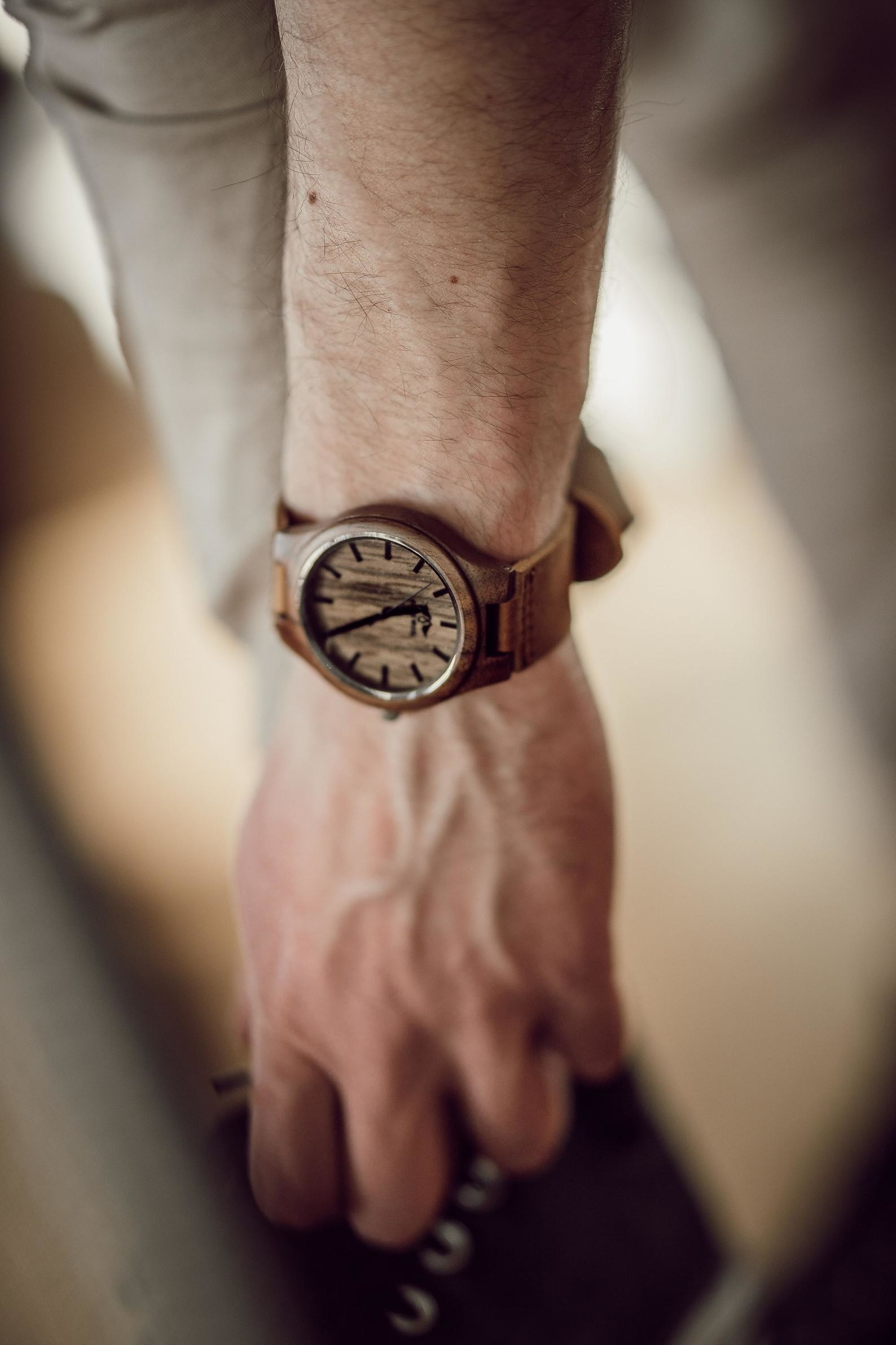 arm with wooden watch on