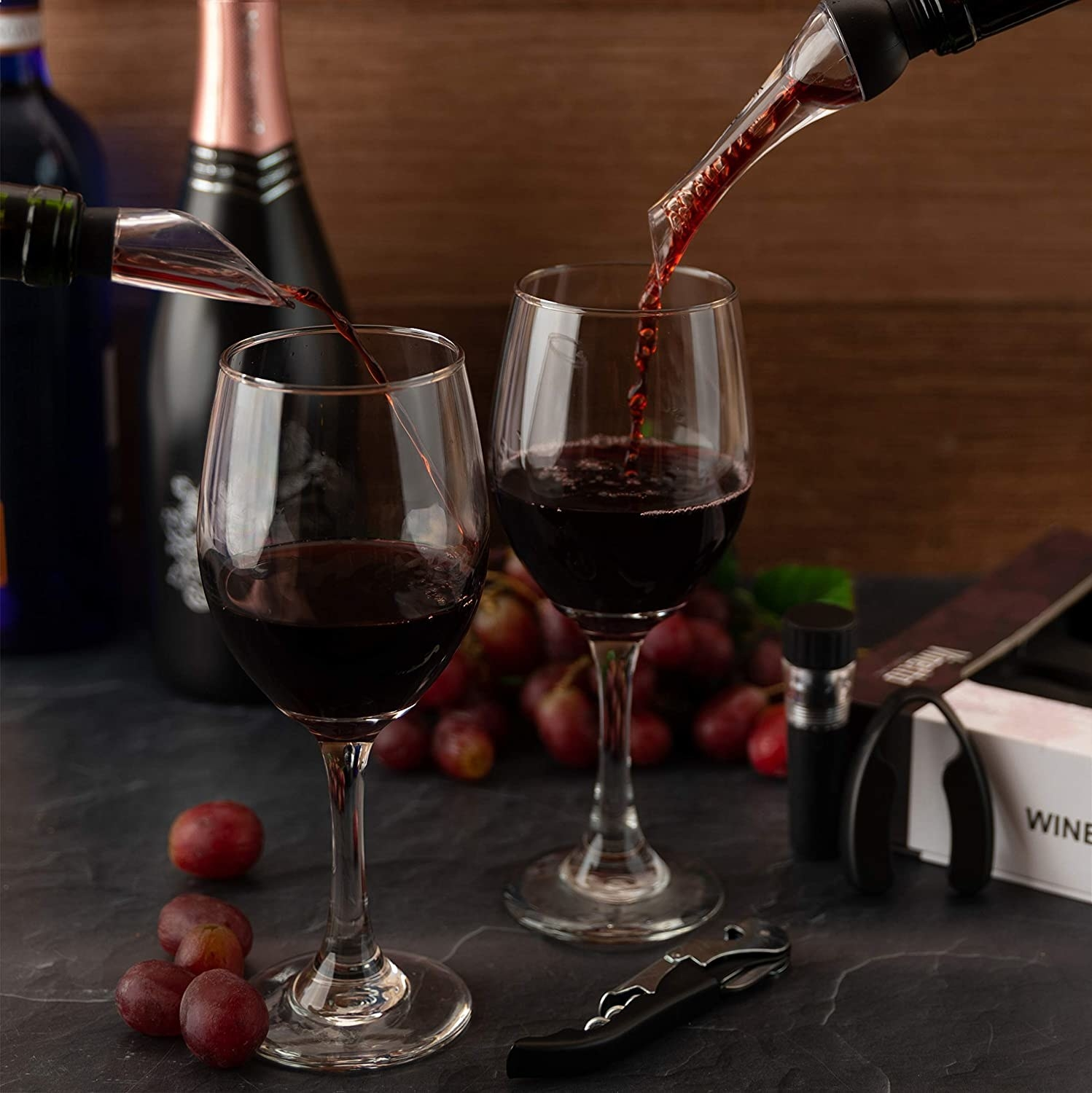 A bottle of wine with an aerator on it pours wine into a glass