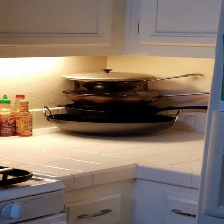 The organizer holding four pans upright in the corner of a kitchen counter
