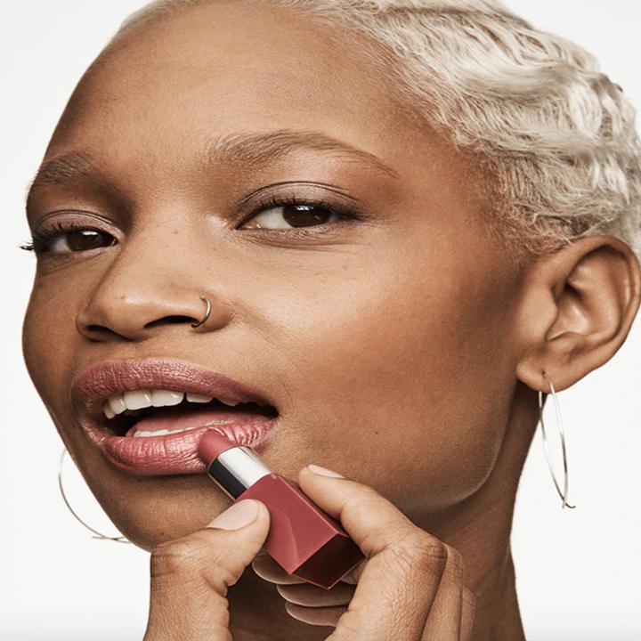 a model applying one of the lipsticks