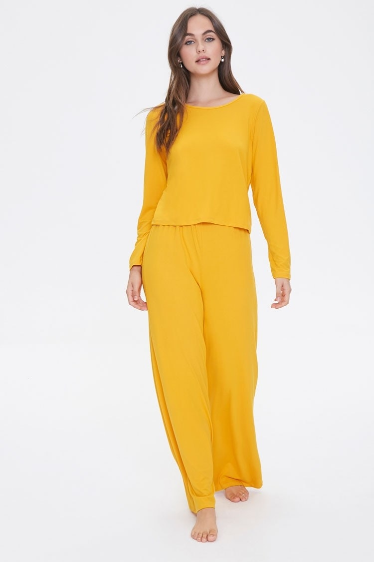 a model in flowy pants and top in sunshine yellow