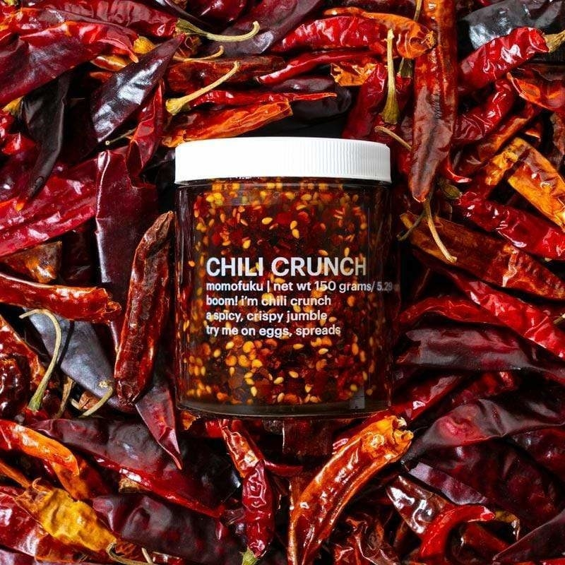 the jar of chili crunch on a bed of chili peppers