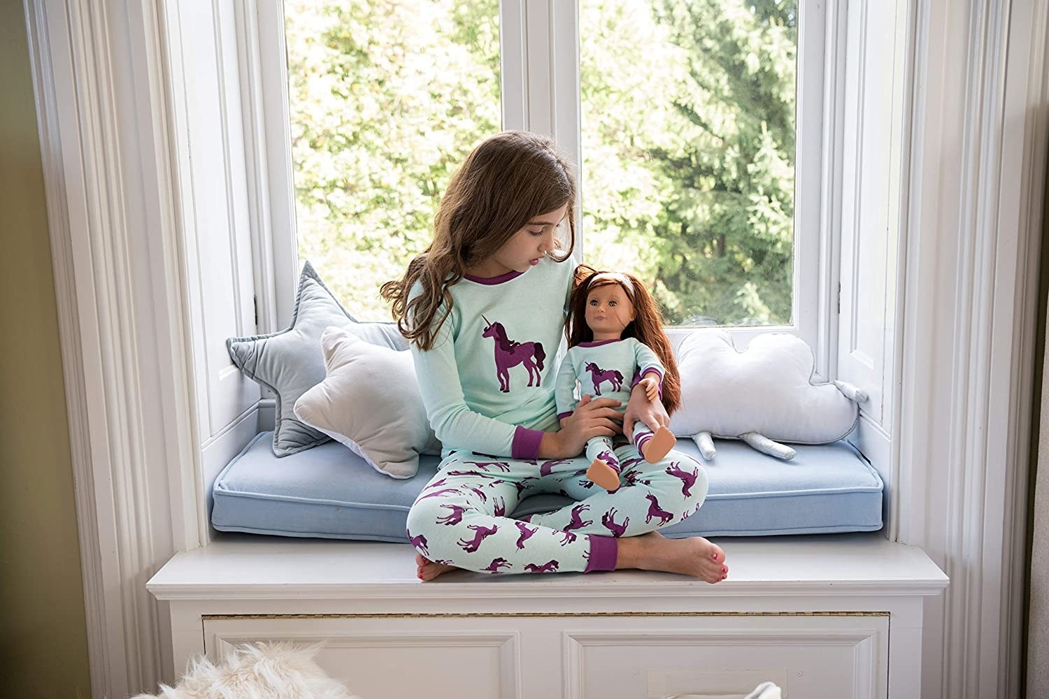 a child and her doll in matching unicorn pajamas