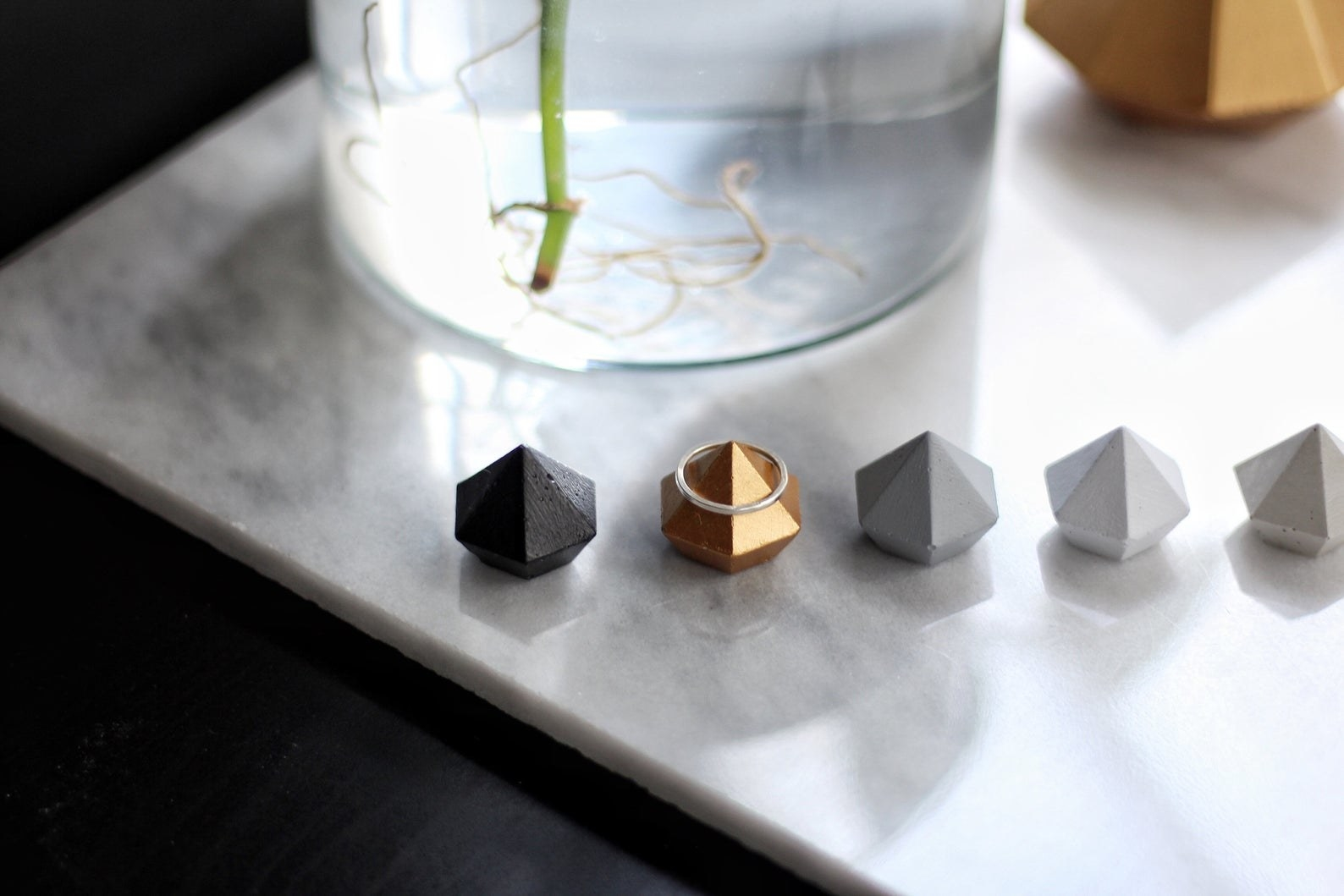 five ring holders with a ring on one of them